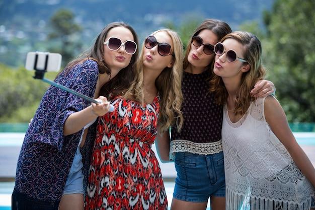Mulheres bonitas tomando uma selfie perto da piscina