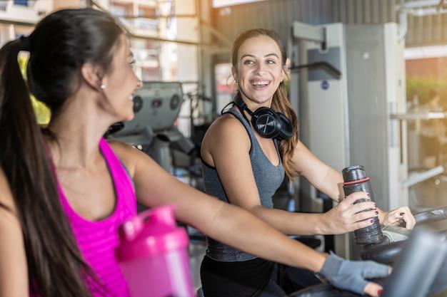 Mulheres bonitas, treinando em uma academia. grupo bonito de amigos das jovens mulheres que exercitam em uma escada rolante no gym moderno brilhante.