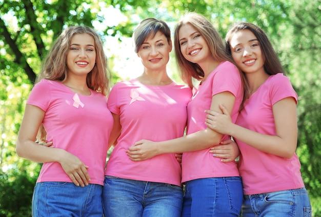 Mulheres bonitas usando camisetas com fitas rosa, ao ar livre