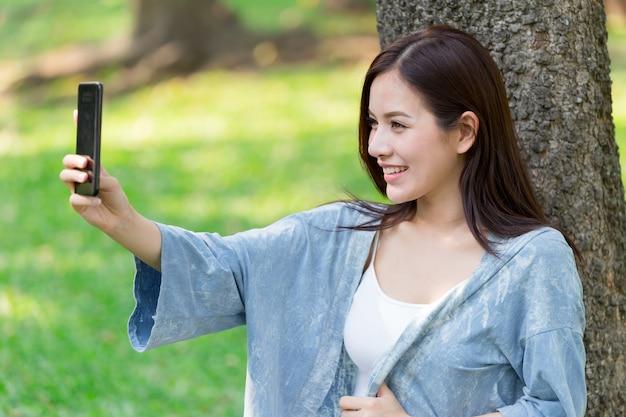Mulheres bonitos asiáticas com smartphone selfie no parque