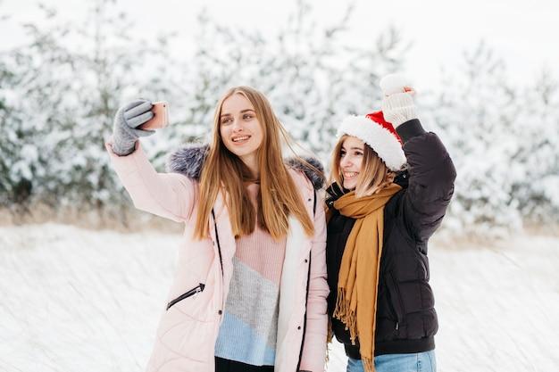 Mulheres bonitos no chapéu de papai noel tomando selfie na floresta de inverno