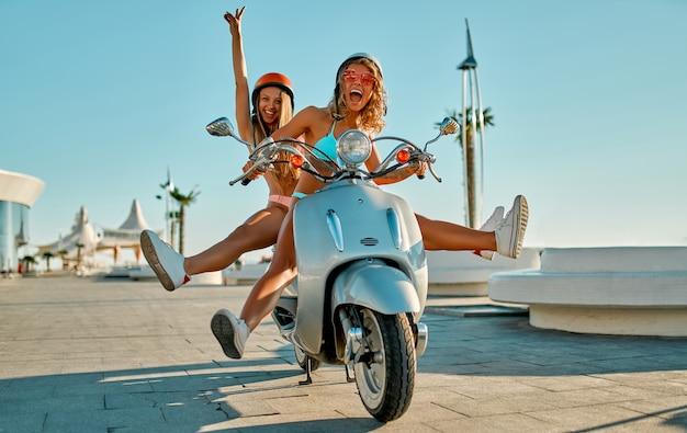 Mulheres brancas em trajes de banho de biquíni com capacetes de segurança estão se divertindo em uma bicicleta perto da praia em um dia ensolarado.
