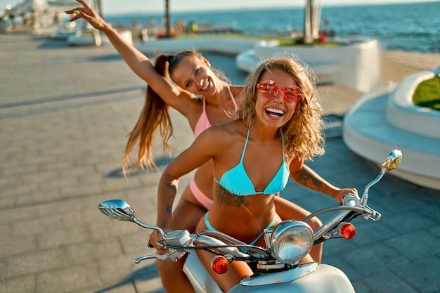 Mulheres brancas em trajes de banho de biquíni estão se divertindo em uma bicicleta perto da praia em um dia ensolarado.