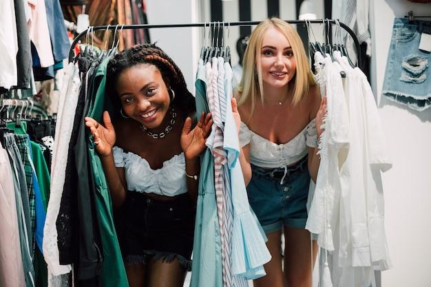 Mulheres brincalhão na loja de roupas
