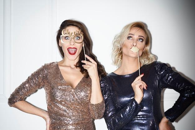 Mulheres brincalhonas em festa na cabine fotográfica