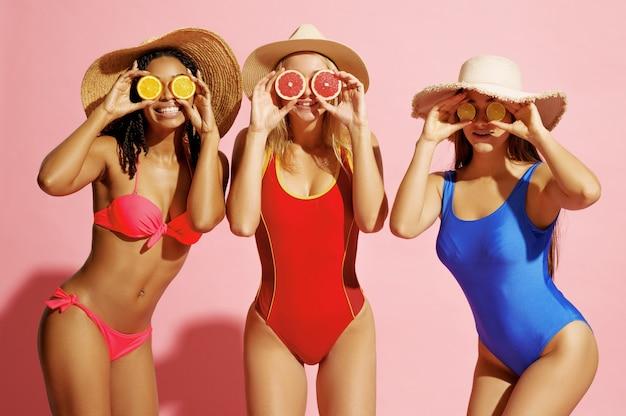 Mulheres brincalhonas em trajes de banho e chapéus posam com frutas em rosa