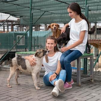 Mulheres brincando com cães de resgate de cura em abrigo