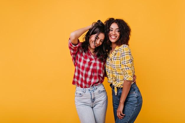 Mulheres bronzeadas emocionais posam alegremente em camisas xadrez. retrato de morenas com cabelos cacheados.