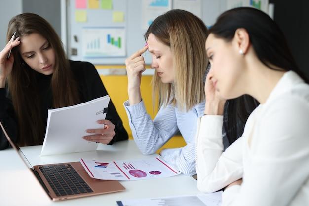 Mulheres cansadas sentadas à mesa com documentos nas mãos
