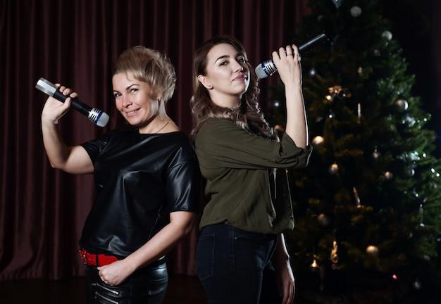 Mulheres cantam no palco em microfones de karaokê contra a árvore de natal