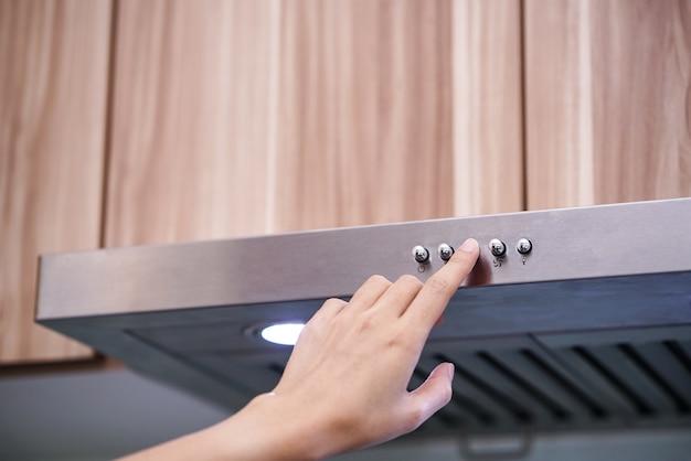 Mulheres caucasianas mão usando o exaustor na cozinha moderna