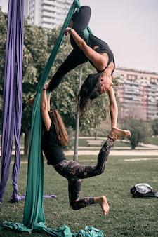 Mulheres caucasianas praticando algumas posições difíceis de sedas aéreas juntas em um parque da cidade