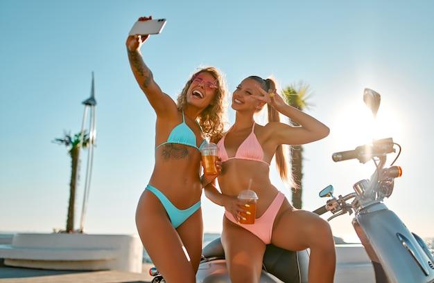Mulheres caucasianos em trajes de banho de biquíni estão se divertindo tomando selfie em smartphone perto de bicicleta na praia em um dia ensolarado.