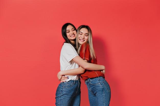Mulheres charmosas de cabelos compridos sorrindo e se abraçando contra uma parede vermelha