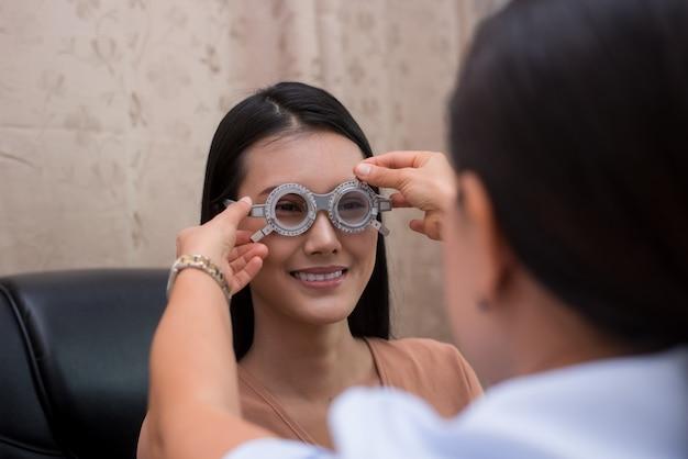 Mulheres chinesas que fazem o exame de olhos em uma loja ótica. consulta com um oftalmologista.