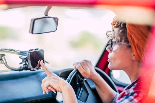 Mulheres colocam e usam o navegador de mapas de satélite celular dentro do carro para viajar e chegar a destinos - mulher e tecnologia de navegação para dirigir e desfrutar de transporte - jovem usa automóvel