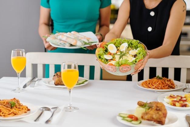 Mulheres colocando uma tigela de deliciosa salada de vegetais e rolinhos primavera na mesa de jantar
