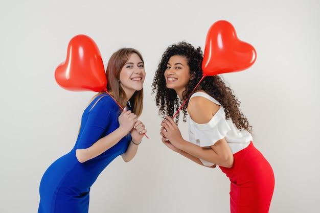 Mulheres com balões em forma de coração vermelho sorrindo isolado