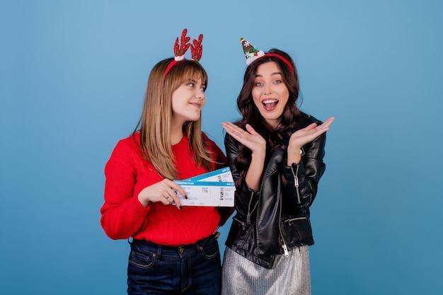Mulheres com bilhetes de avião usando aros de feriado de ano novo isolados