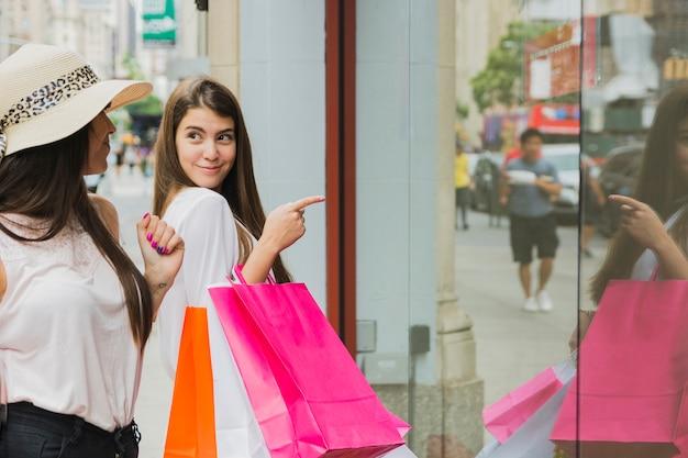 Mulheres, com, bolsas para compras, perto, vitrina