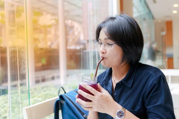 Mulheres com cabelo curto. sente-se junto ao vidro da janela, bebendo flores de ervilha de água.