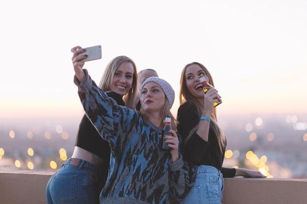 Mulheres com cerveja tomando selfie no telhado