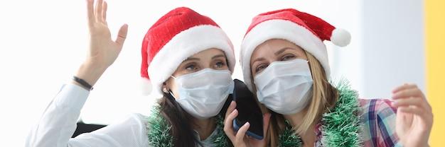 Mulheres com chapéu de papai noel vermelho e máscaras médicas protetoras falando ao celular em casa