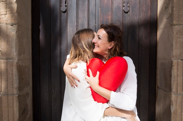Mulheres, com, coração exuberante, abraçando, perto, madeira, porta