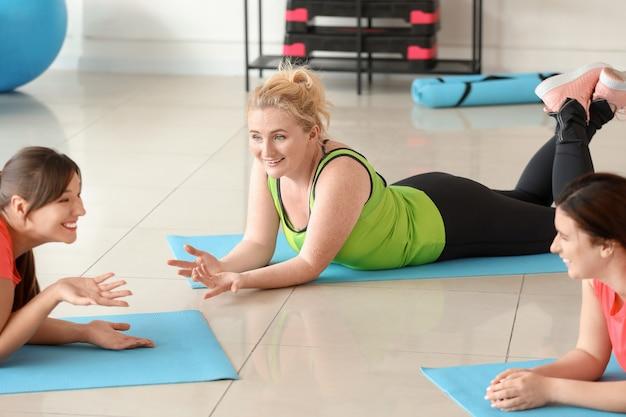 Mulheres com corpo positivo descansando após treino na academia