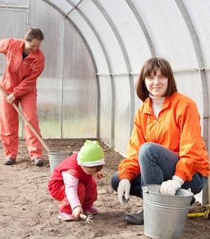 Mulheres com criança trabalham na estufa