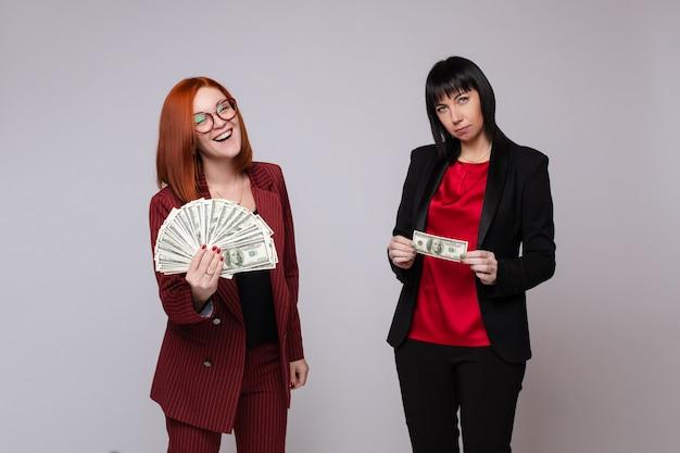 Mulheres com dinheiro posando na parede cinza