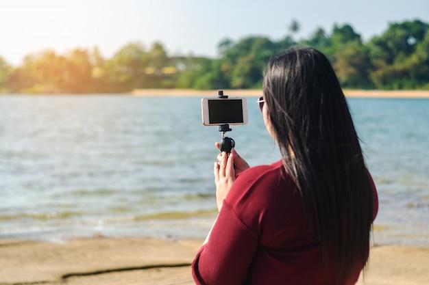 Mulheres, com, esperto, telefone móvel, em, seascape, natureza, fundo