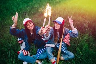 Mulheres, com, fogos artifício, em, mãos, sorrindo