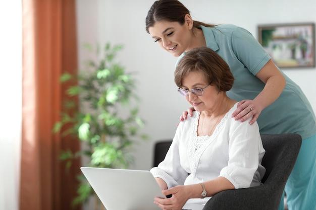Mulheres com laptop dentro de casa tiro médio