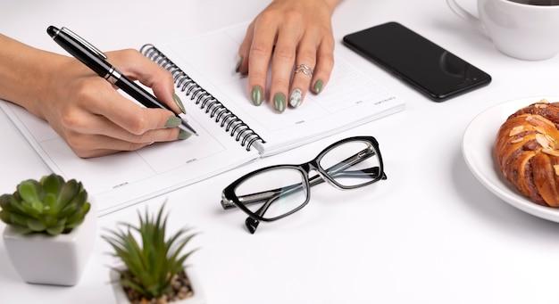 Mulheres com mãos bem cuidadas, com design de unhas verde primavera verão, escrevem em planejador