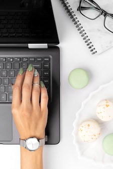 Mulheres com mãos bem cuidadas, com design de unhas verde primavera verão no teclado