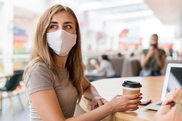 Mulheres com máscara trabalhando e bebendo café