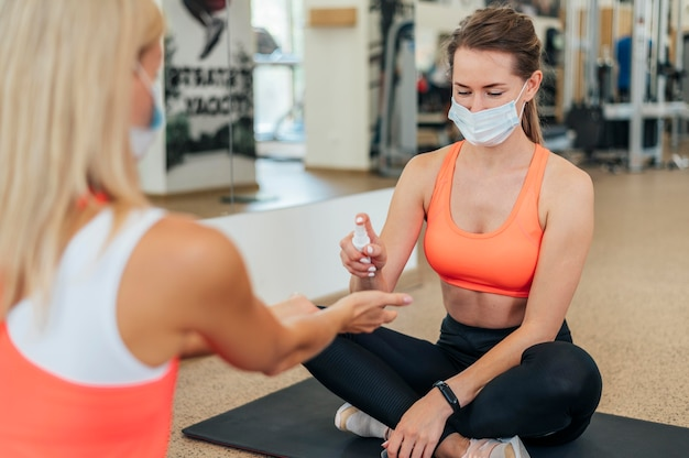 Mulheres com máscaras médicas desinfetando as mãos na academia