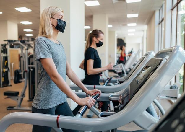 Mulheres com máscaras médicas usando equipamentos de ginástica