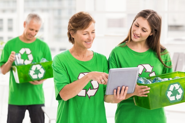 Mulheres com mentalidade ecológica com tableta e caixa de reciclagem