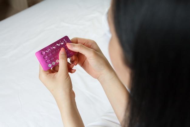 Mulheres com pílulas anticoncepcionais nas mãos