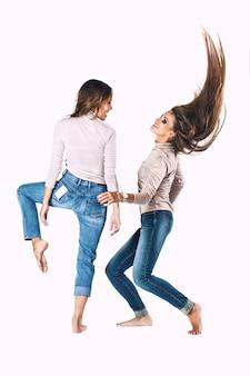 Mulheres com roupas da moda em jeans no estúdio em uma parede branca em várias poses