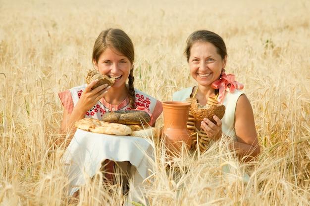 Mulheres com roupas tradicionais com pão