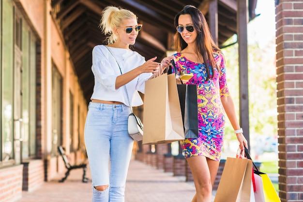 Mulheres com sacos olhando para smartphone e indo na rua comercial