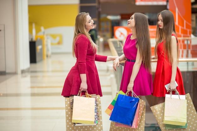 Mulheres com salto alto e sacolas de compras