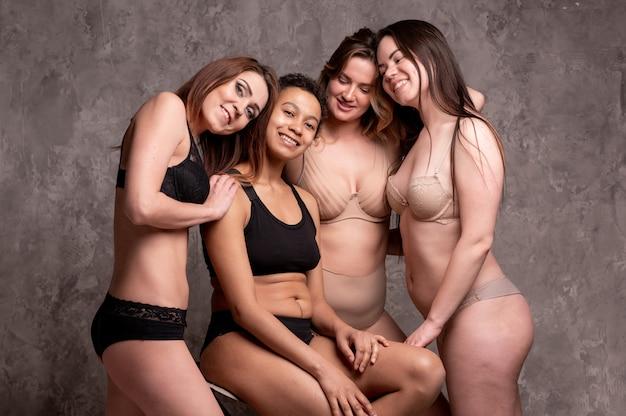 Mulheres com sobrepeso e magro bonitas em um maiô bege e preto sobre um fundo cinza. corpo positivo. size plus