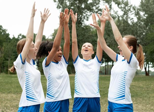 Mulheres com tiro médio de mãos erguidas