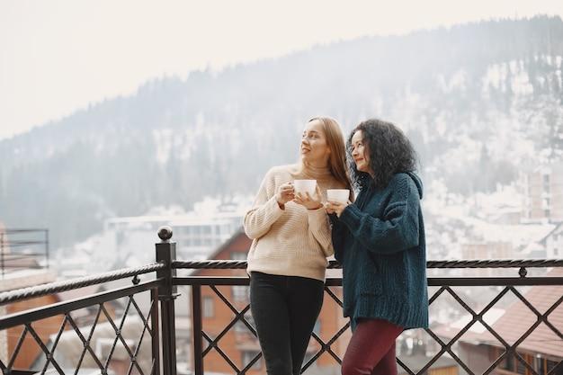 Mulheres com uma xícara de café. férias maravilhosas nas montanhas. tempo com neve.