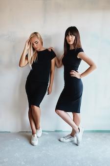 Mulheres com vestido posando na parede