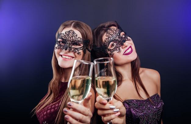Mulheres comemorando a véspera de ano novo, bebendo champanhe na festa de máscaras